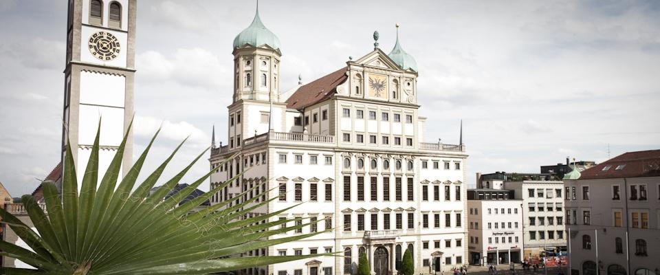 Blick auf Rathaus Augsburg mit Palme im Vordergrund