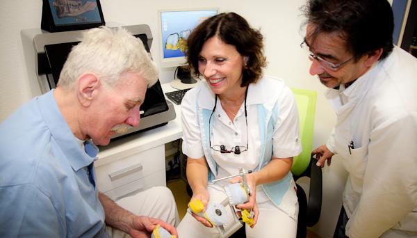 Die Zahnärzte betrachten gemeinsam mit dem Zahntechniker ein Kiefermodell